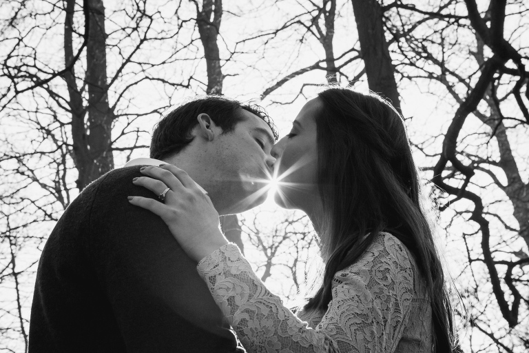 Black and white of a couple kissing with the sun between them